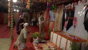 Люди кланяются перед изображением Махарадж-джи